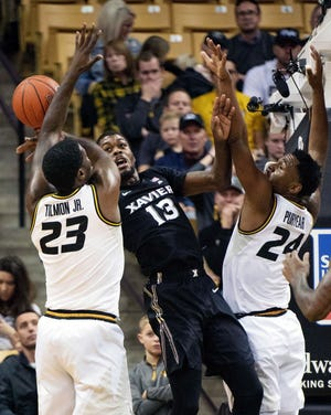 Xavier's Naji Marshall, center, bobbles a pass between Missouri's Jeremiah Tilmon, left, and Kevin Puryear, right, during the first half of an NCAA college basketball game Tuesday, Dec. 18, 2018, in Columbia, Mo.
