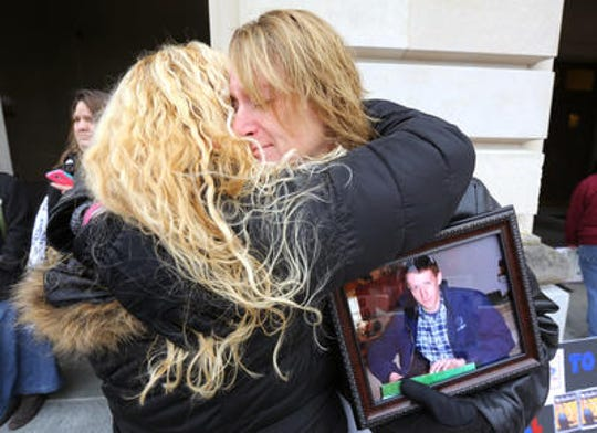 Rhonda Dupuy of Dry Ridge, right, accepts a hug from Pennie Tackett of Taylor Mill as Dupuy clutches a photo of her son, Coty Glass. Glass died from an overdose at 22 years old in 2014.