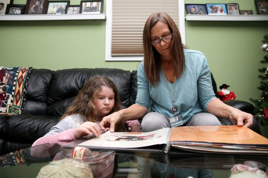 Katie, 11, left, and Mary Freeman, work on a scrap book, Tuesday, Dec. 18, 2018, at their home in Colerain Township.