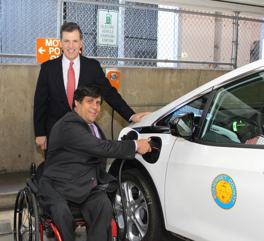 Freeholder Mark Caliguire looks on as Freeholder Director Patrick Scaglione demonstrates the charging system for one of four new Chevy Bolt electric vehicles added to the county's fleet.