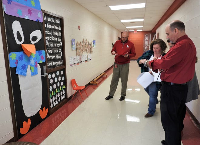 Coshocton Elementary School had a first ever door decorating contest for Christmas. Judges were high school Principal Grant Fauver, Director of Curriculum Kaitlyn Ashbrook and Superintendent David Hire. Second from left is Literacy Coach Megan Crook, one of the contest organizers.