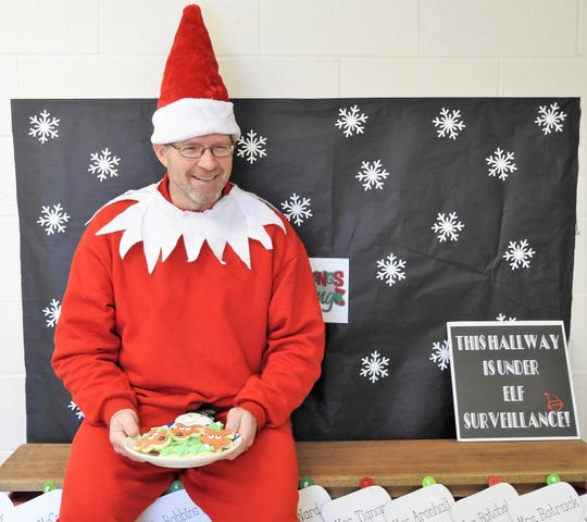 Sixth grade teacher Tim Ward dressed as the Elf on a Shelf and passed out cookies during judging of a Christmas door decoration contest at Coshocton Elementary School.