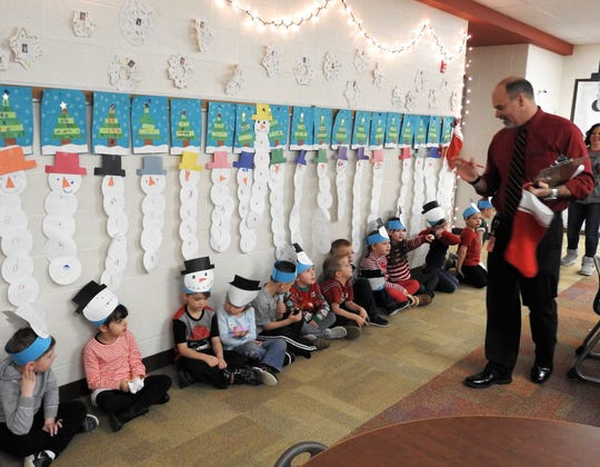 Coshocton City Schools Superintendent David Hire is greeted by kindergarten students as he and other judges go down the hall for a Christmas door decorating contest at Coshocton Elementary School. Kindergarten won best overall.