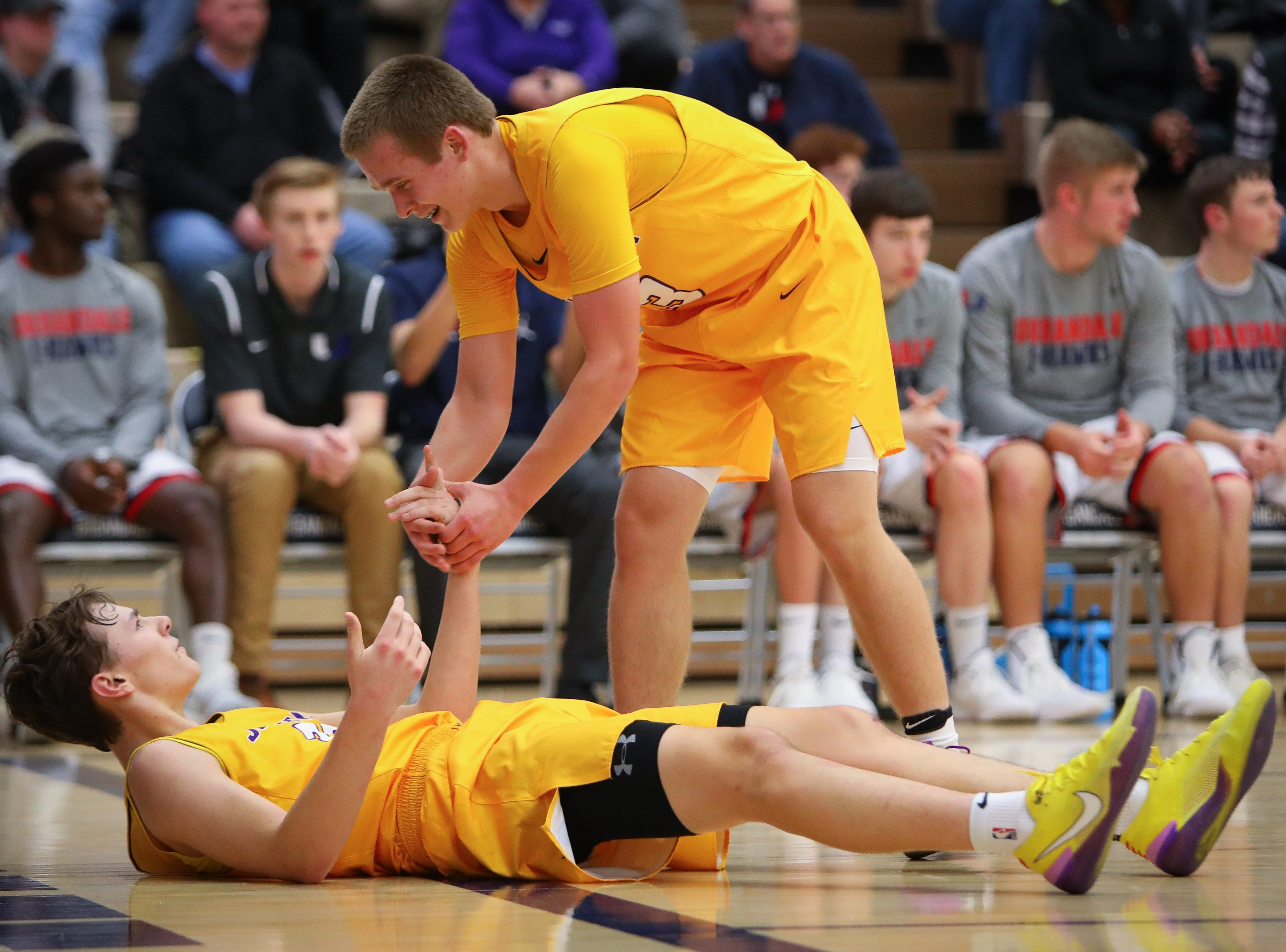 Johnston freshman Jacob Runayn helps sophomore Reid Grant up during a boys high school basketball game between the Johnston Dragons and the Urbandale J-Hawks at Urbandale High School on Dec. 18, 2018 in Urbandale, Iowa.