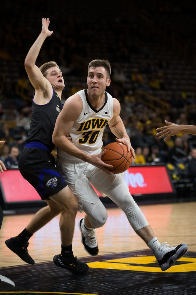 Iowa redshirt freshman guard Connor McCaffery (30) drives against Western Carolina sophomore guard Matt Halvorsen (2) in the second half at Carver Hawkeye Arena in Iowa City on Tuesday, Dec. 18, 2018.