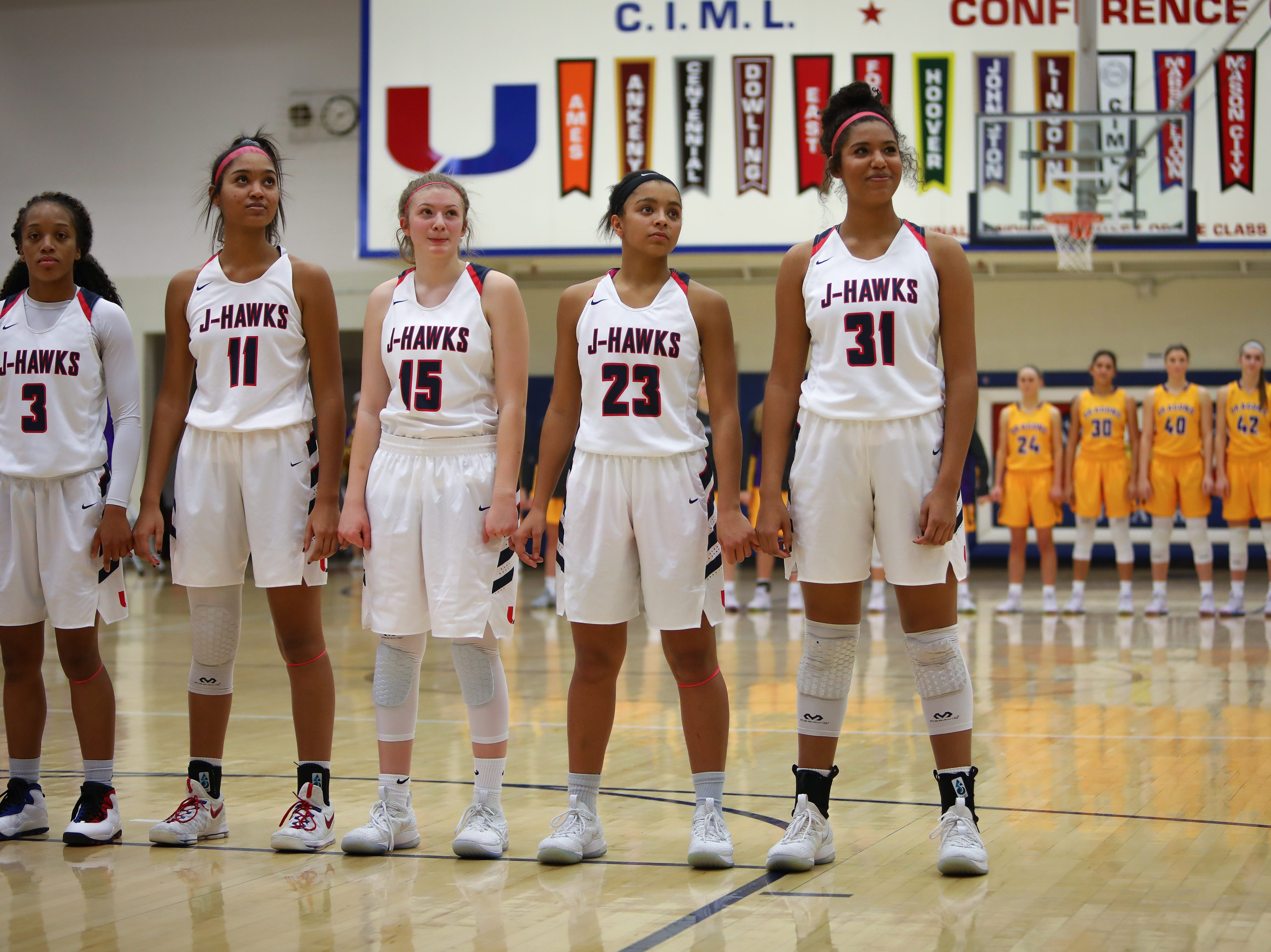 Members of the Urbandale J-Hawks and the Johnston Dragons line up for the national anthem before a girls high school basketball game at Urbandale High School on Dec. 18, 2018 in Urbandale, Iowa.