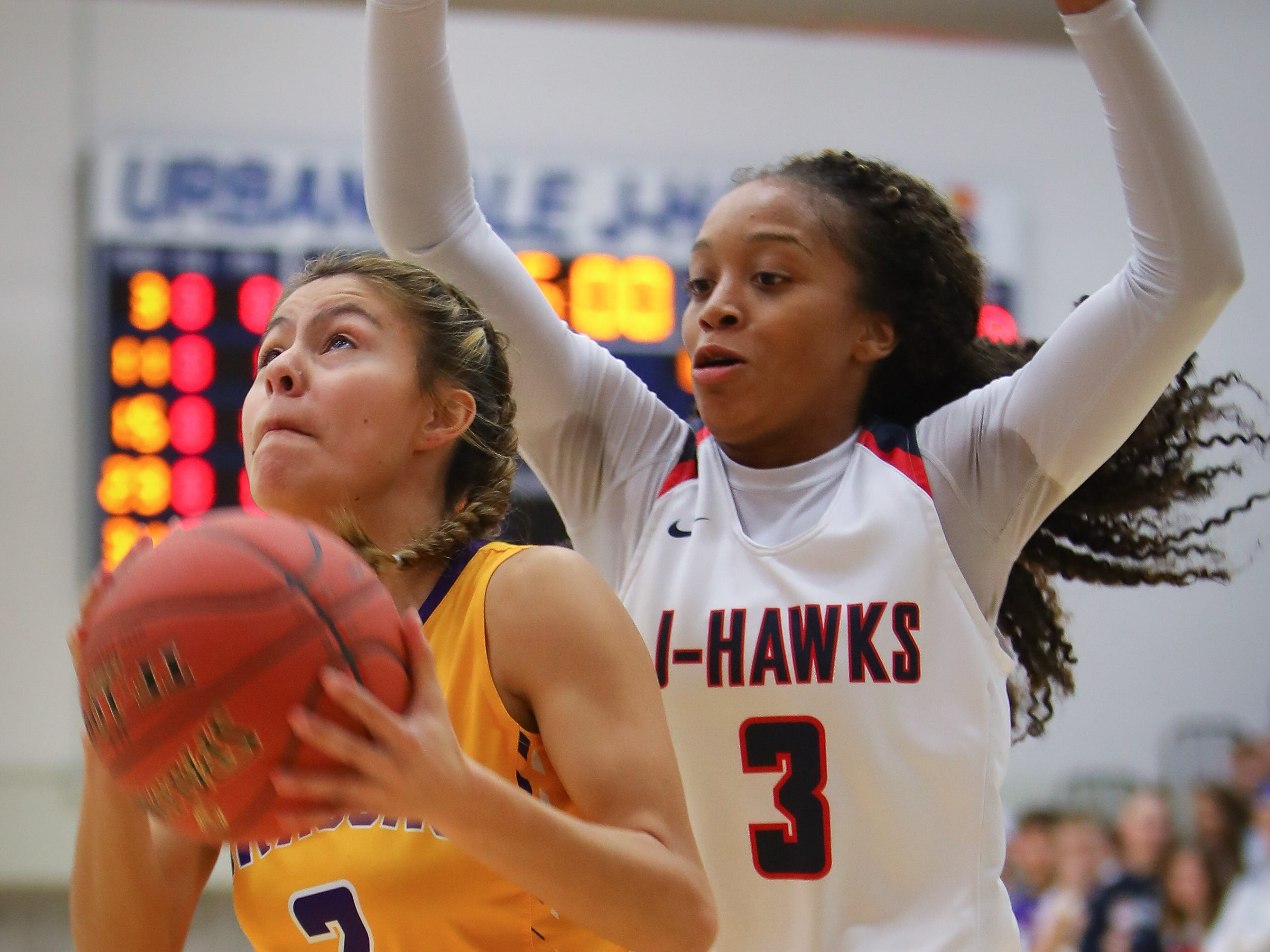 Johnston junior Maya McDermott goes for a field goal as Urbandale senior Dee Dee Pryor attempts to block the shot during a girls high school basketball game between the Johnston Dragons and the Urbandale J-Hawks at Urbandale High School on Dec. 18, 2018 in Urbandale, Iowa.