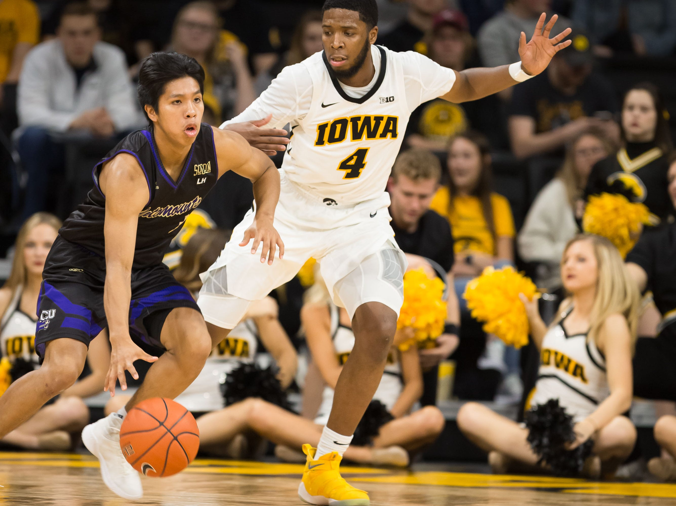 Western Carolina junior guard Jason McMillan (3) dribbles past Iowa junior guard Isaiah Moss (4) in the second half at Carver Hawkeye Arena in Iowa City on Tuesday, Dec. 18, 2018.