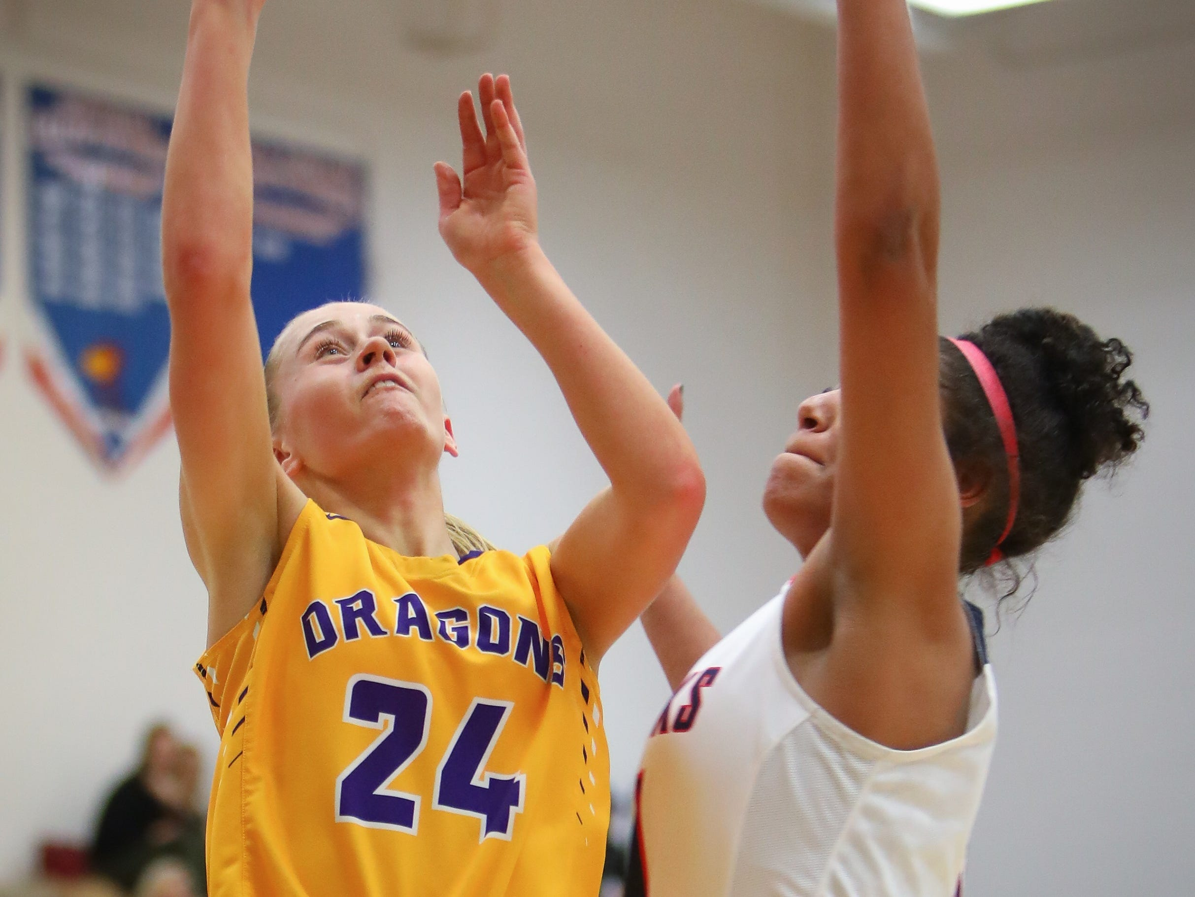 Johnston senior Macy Thompson goes for a layup over Urbandale junior Faith Putz during a girls high school basketball game between the Johnston Dragons and the Urbandale J-Hawks at Urbandale High School on Dec. 18, 2018 in Urbandale, Iowa.