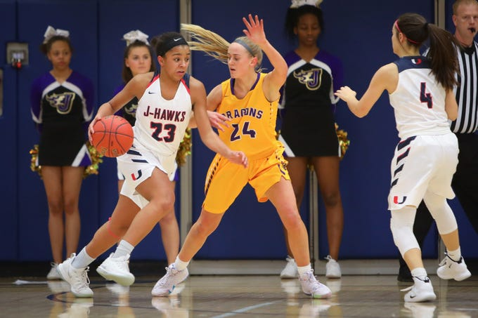Urbandale junior Faith Putz drives the ball past Johnston senior Macy Thompson during a girls high school basketball game between the Johnston Dragons and the Urbandale J-Hawks at Urbandale High School on Dec. 18, 2018 in Urbandale, Iowa.