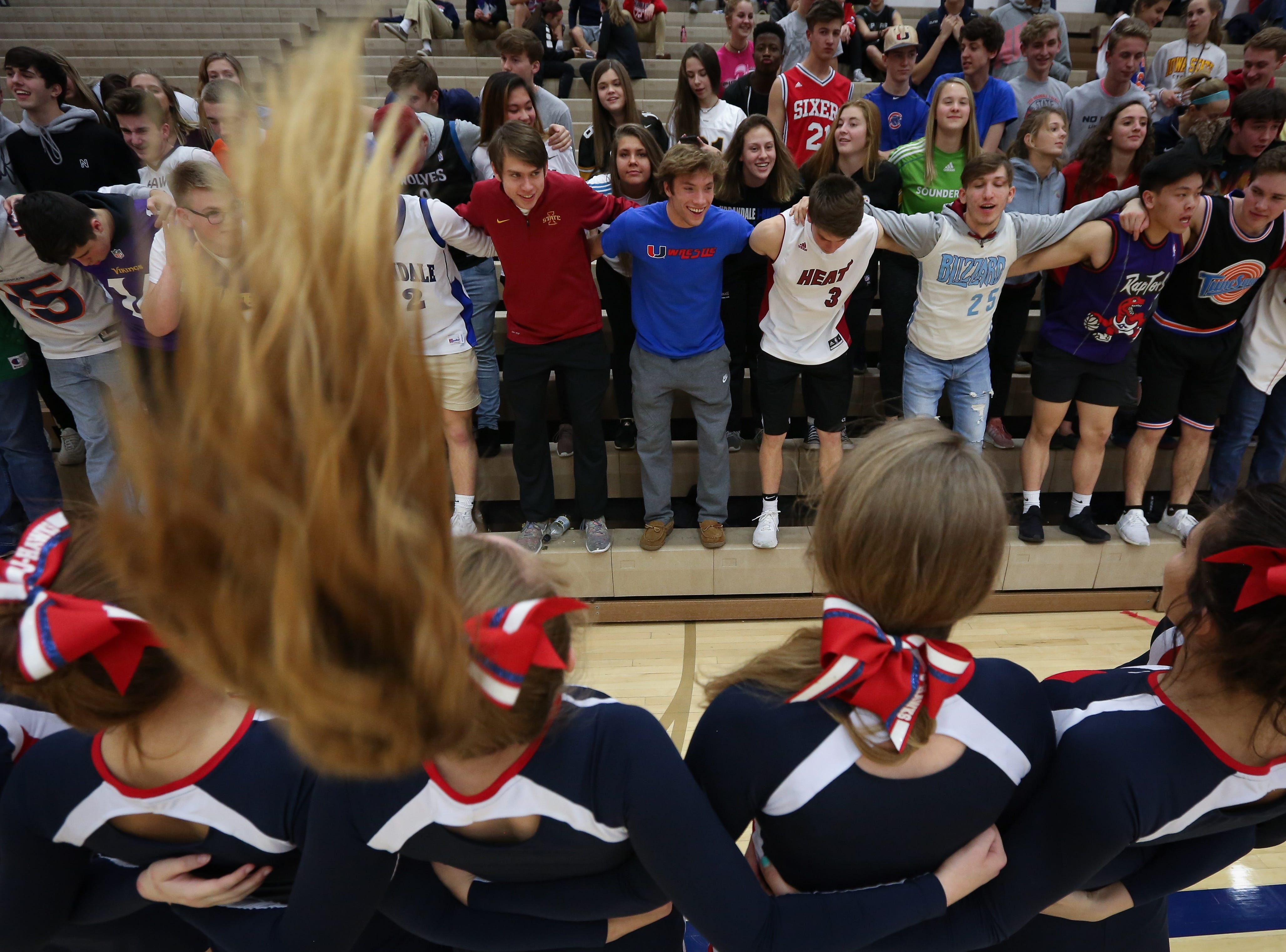 Urbandale cheerleaders lead a chant with student fans during a boys high school basketball game between the Johnston Dragons and the Urbandale J-Hawks at Urbandale High School on Dec. 18, 2018 in Urbandale, Iowa.