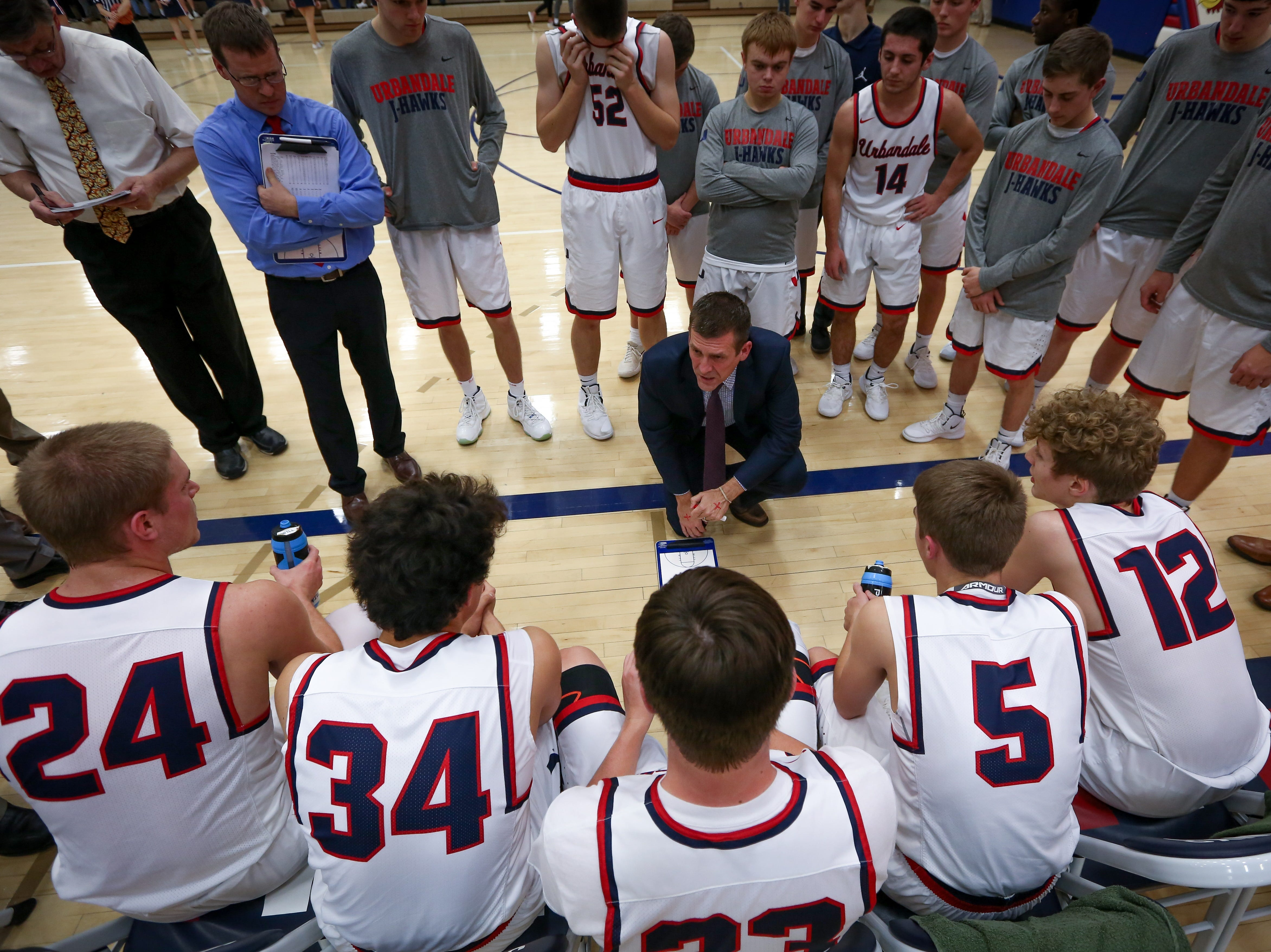 Urbandale head coach Jon Schmitz goes over plays during a timeout in a boys high school basketball game between the Johnston Dragons and the Urbandale J-Hawks at Urbandale High School on Dec. 18, 2018 in Urbandale, Iowa.