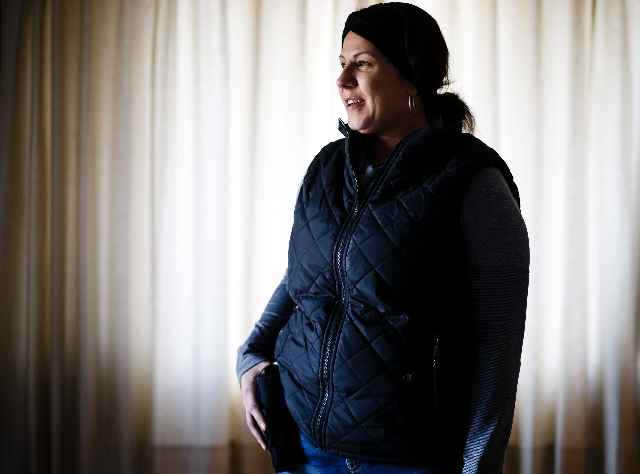 Jessica Bensley admits she has misdemeanors in her past but none that have risen to the level of a felony. Despite that, Bensley, along with others, were inaccurately added year to an Iowa felon list, resulting in the rejection of their votes. A licensed concealed-carry gun owner, Bensley poses with her sidearm at her home on Wednesday, Dec. 19, 2018, in Des Moines.