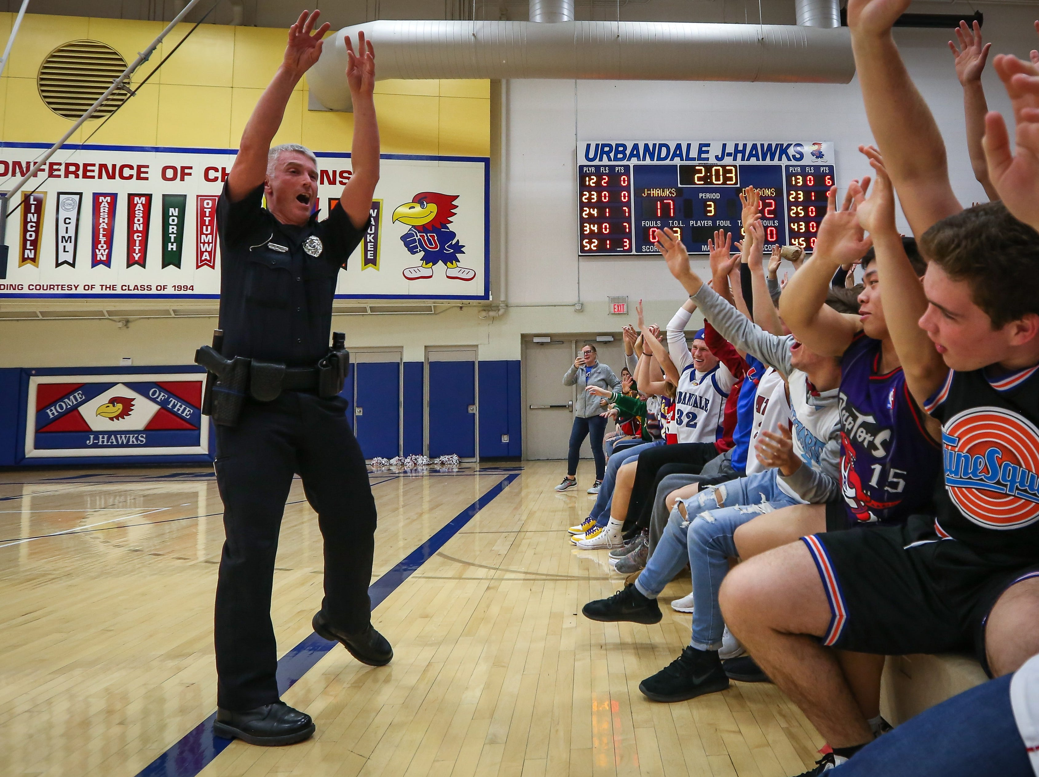 Urbandale school resource officer Eric Wilcutt leads a cheer with student fans during a boys high school basketball game between the Johnston Dragons and the Urbandale J-Hawks at Urbandale High School on Dec. 18, 2018 in Urbandale, Iowa.