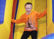 Jackson Powell, 7, of Ankeny, makes his way down an inflatable slide at The Playground For Kids in Ankeny in this 2011 file photo.