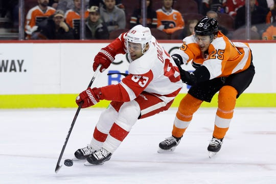 Philadelphia Flyers' James van Riemsdyk, right, hooks Detroit Red Wings' Trevor Daley during the first period of an NHL hockey game, Tuesday, Dec. 18, 2018, in Philadelphia.