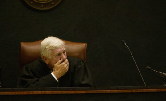 Judge John McDonald looks at autopsy photos during the first day of the first degree murder trial of Nancy Seaman on November 30, 2004.