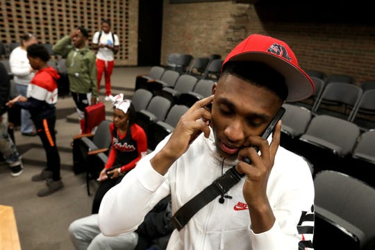 Oak Park High School quarterback Dwan Mathis works two cell phones while answering reporters questions after he selected the University of Georgia over Ohio State during signing day on Wednesday, December 19, 2018 at the school in Oak Park.