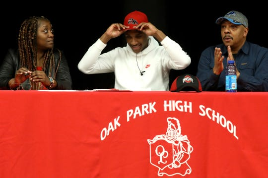 Flanked by his parents Dawn McFarlin and Terence Mathis, Oak Park quarterback Dwan Mathis tries a University of Georgia hat on for size as he picks Georgia over Ohio State during signing day on Wednesday, December 19, 2018 at the school in Oak Park.
