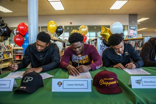 From left, Jalen Graham, Lewis Nichols and Marcellus Gaines sign letters of intent to play college football with Purdue University, Central Michigan University, and Morgan State University, during signing day at Cass Technical High School in Detroit on Wednesday, Dec. 19, 2018.