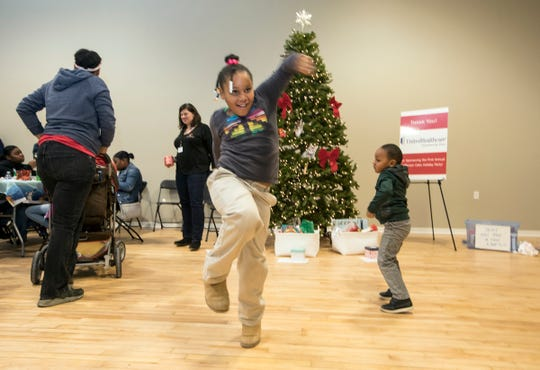 Faith Rivers, 6, and her brother Drew Rivers, 3, dance to Christmas songs earlier this month during an open house for residents of Jefferson Oaks, a new affordable apartment and townhome development in Oak Park.