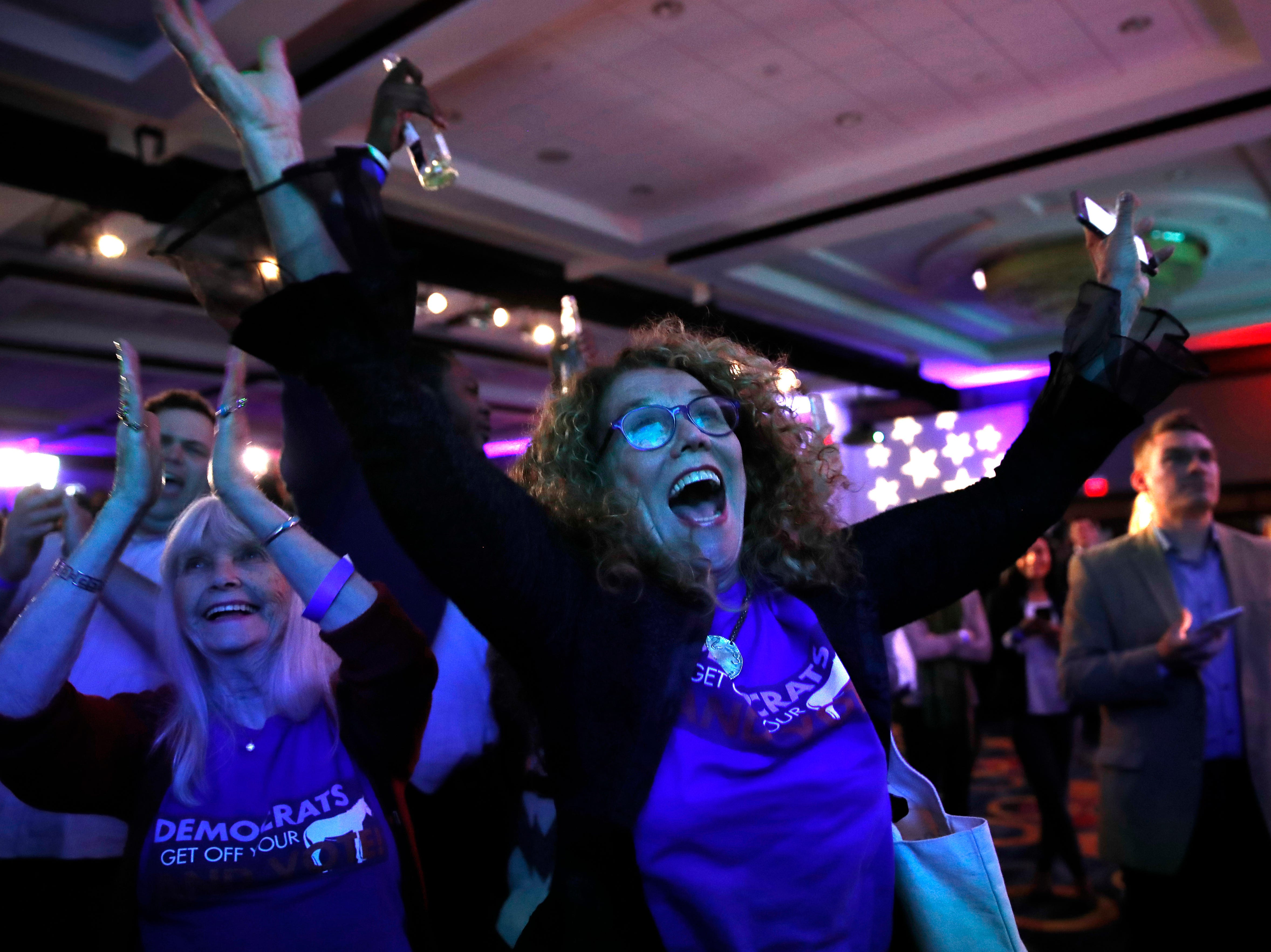 Sydney Crawford, 84, left, of New York, and JoAnn Loulan, 70, of Portola Valley, Calif., cheer as election returns come in during a Democratic party election night event at the Hyatt Regency Hotel in Washington on Tuesday, Nov. 6, 2018.