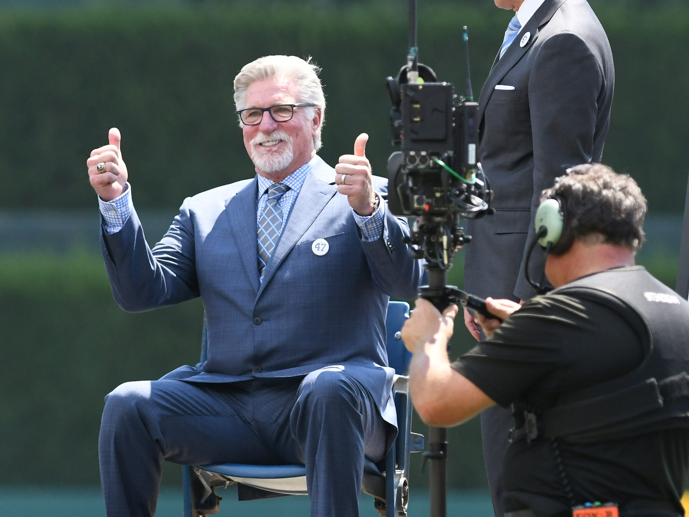 Former Detroit Tigers pitcher Jack Morris gives two thumbs up while sitting in his #47 seat from Tiger Stadium, a gift from Chris Ilitch (right) during a  pregame ceremony to retire the Morris' #47 jersey on August 12, 2018 at Comerica Park in Detroit. Morris and 1984 World Series Tigers teammate Alan Trammell were inducted into the Major League Baseball Hall of Fame in 2018.