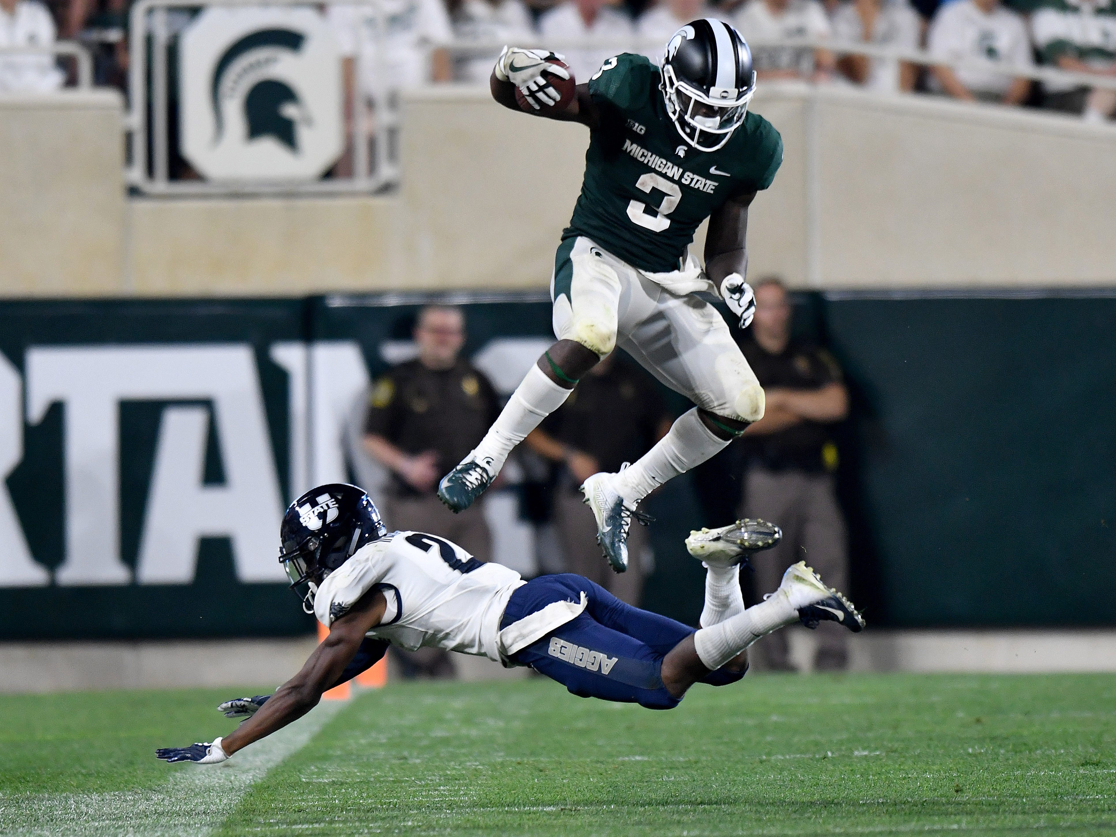 Michigan State running back  LJ Scott leaps over would-be Utah State tackler Ja'Marcus Ingram in the fourth quarter of a 38-31 MSU victory in their season opener at Spartan Stadium in East Lansing on Friday, Aug 31, 2018.
