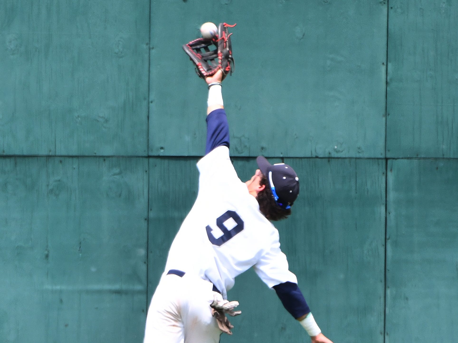 Macomb Dakota outfielder Patrick Merolla appears to catch this long fly ball off the bat of Grosse Pointe South High School's Logan Maclean during an  MHSAA baseball quarterfinal game at Wayne State University in Detroit, Michigan on June 12, 2018. The ball eluded Merolla on the play and victory eluded Macomb Dakota as G.P. South went on to a  9-1 victory en route to a Div. 1 state title.
