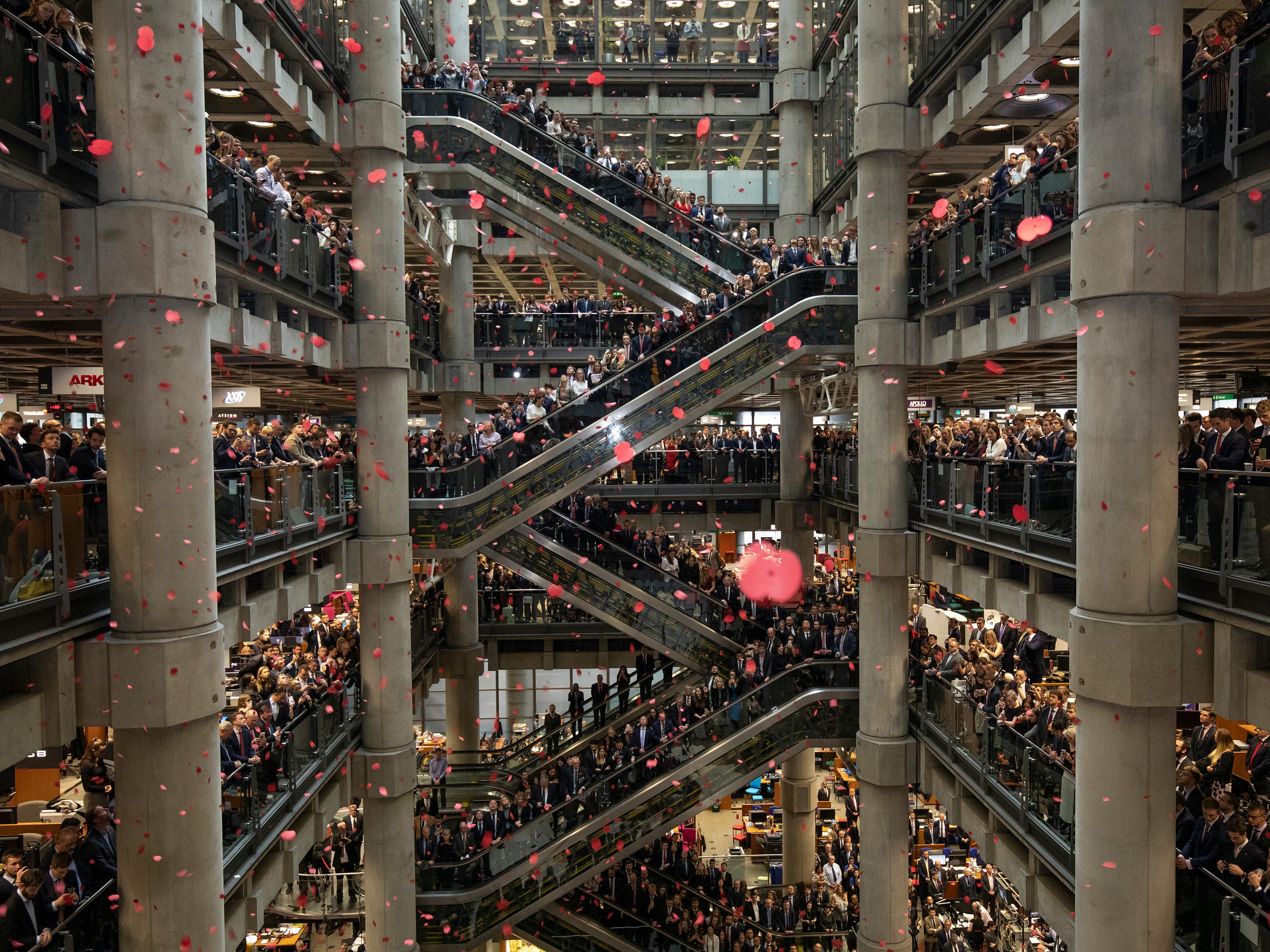 Poppies are dropped as brokers and underwriters line the balconies and escalators of the Lloyd's of London building during a service of remembrance for the veterans of World War I on November 9, 2018 in London, England.  The armistice ending the First World War between the Allies and Germany was signed 100 years ago at Compiégne, France on November 11, 1918.