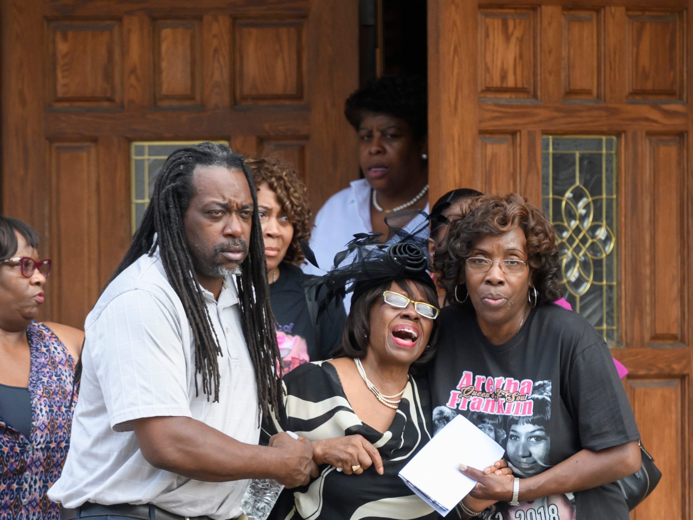 Fannie Tyler, center, long-time personal secretary for Aretha Franklin, is helped out of New Bethel Baptist Church in Detroit  after the public visitation on August 30, 2018.