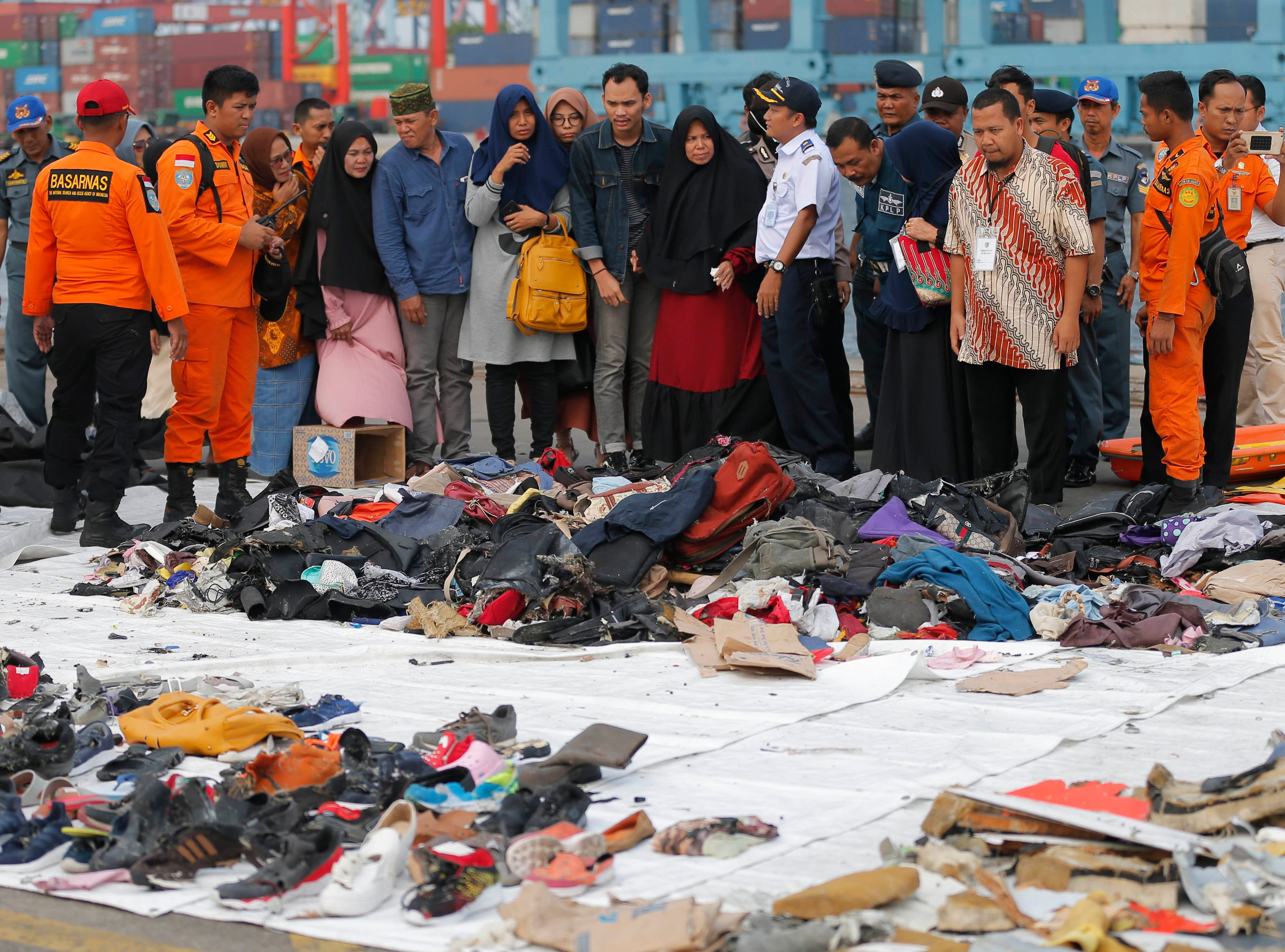 Relatives of passengers on the crashed Lion Air jet check personal belongings retrieved from the waters where the airplane is believed to have crashed, at Tanjung Priok Port in Jakarta, Indonesia, on Oct. 31, 2018.
