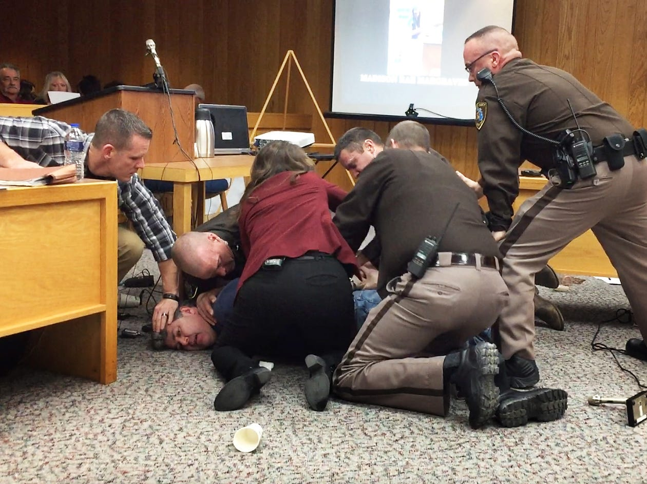 Randall Margraves, father of three of Larry Nassar's sexual assault victims, is tackled by law enforcement officers as he tries to attack Nassar at his sentencing hearing  Feb. 2, 2018 in Charlotte, Michigan.