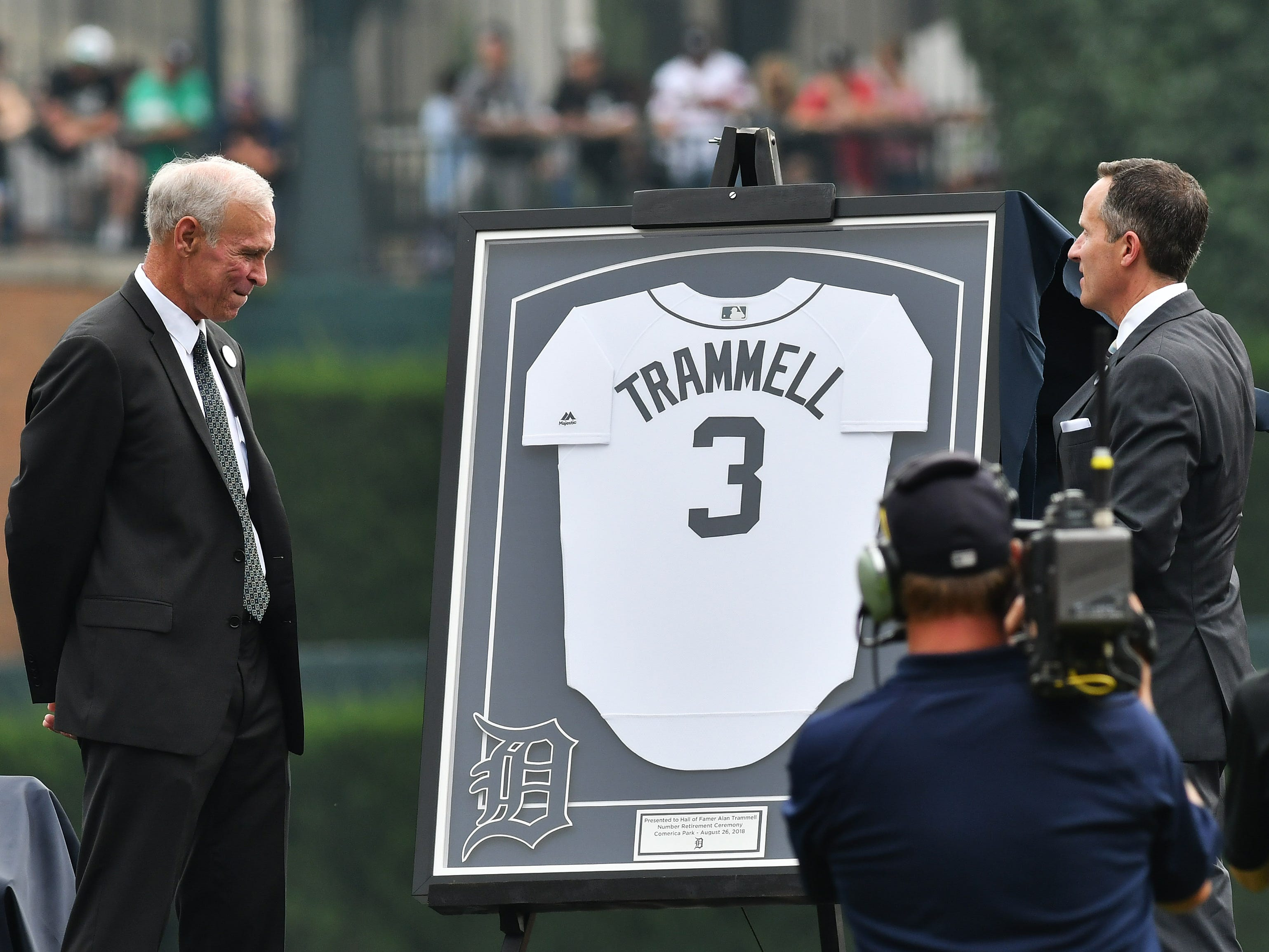 Former Detroit Tigers shortstop Alan Trammell looks on as Chris Ilitch, President and CEO of Ilitch Holdings, presents him with a framed jersey and inscription during a special pregame ceremony to retire the Trammell's #3 jersey before a game at Comerica Park in Detroit on Aug. 26, 2018. Trammell and 1984 World Series champion Detroit Tigers teammate Jack Morris were both  inducted into the Major League Baseball Hall of Fame in 2018.