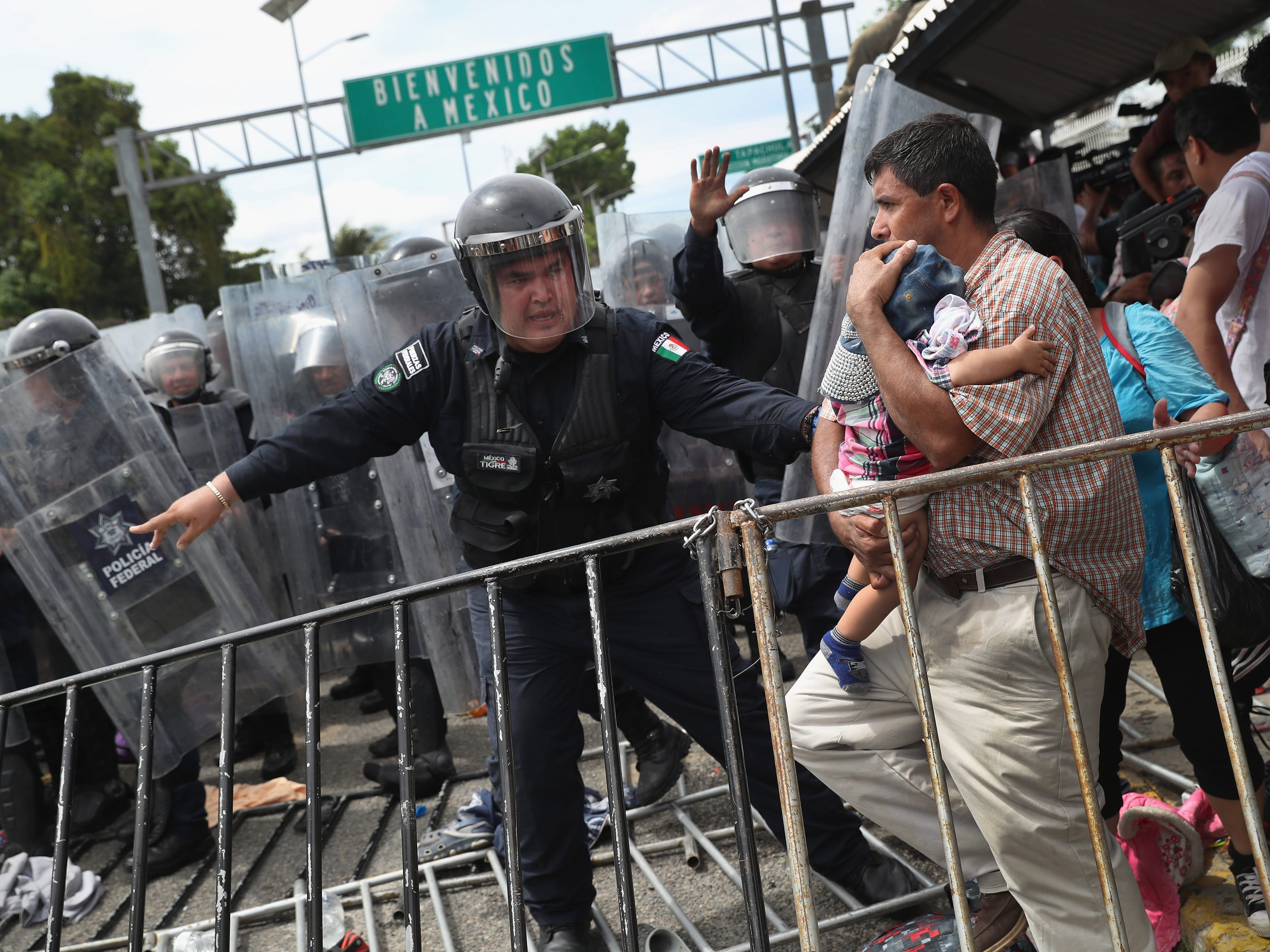 A Mexican riot policeman protects an immigrant father and child during a clash between police and the migrant caravan on the border between Mexico and Guatemala on October 19, 2018 in Ciudad Tecun Uman, Guatemala. A faceoff occurred when the caravan of thousands of migrants tried to enter Mexico after pushing past Guatemalan security forces.
