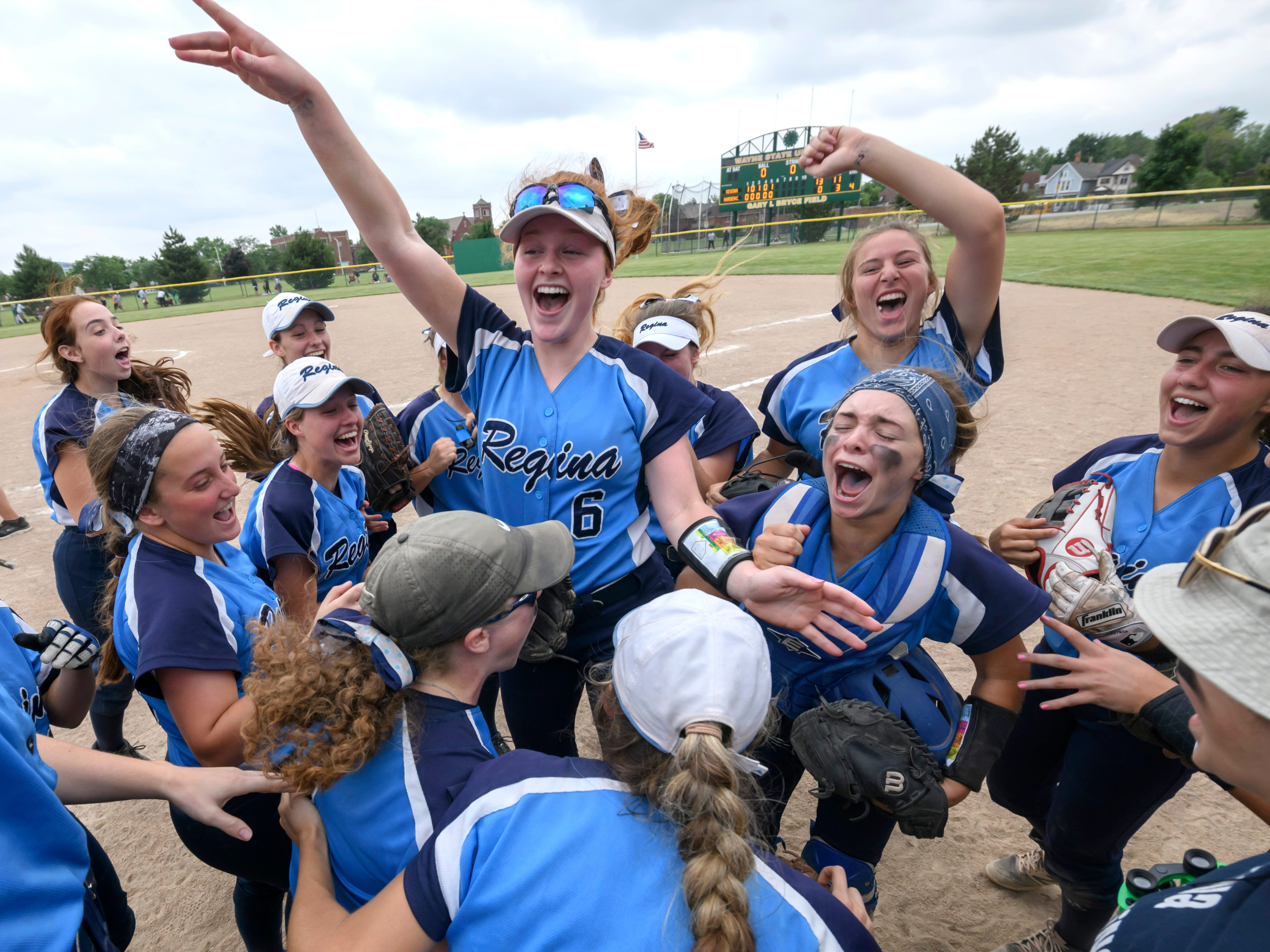 Meghan Berlin (6) and her Warren Regina softball teammates celebrate after defeating Garden City 13-0 during the MHSAA softball quarterfinals at Wayne State University, in Detroit, June 12, 2018. Regina lost 1-0 to eventual division one champions Caledonia.
