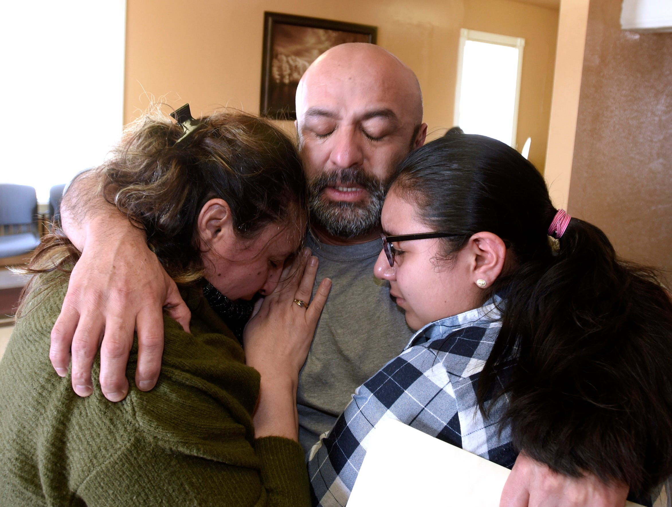 Fernando Lugo-Zarate of Melvindale, center, hugs his wife, Maria Socorro-Lugo, left, and their daughter, Laila Lugo, right, on April 12, 2018. It was the first time they had been together since March 18, when the parents were arrested at their home in a sweep of undocumented immigrants in Metro Detroit.