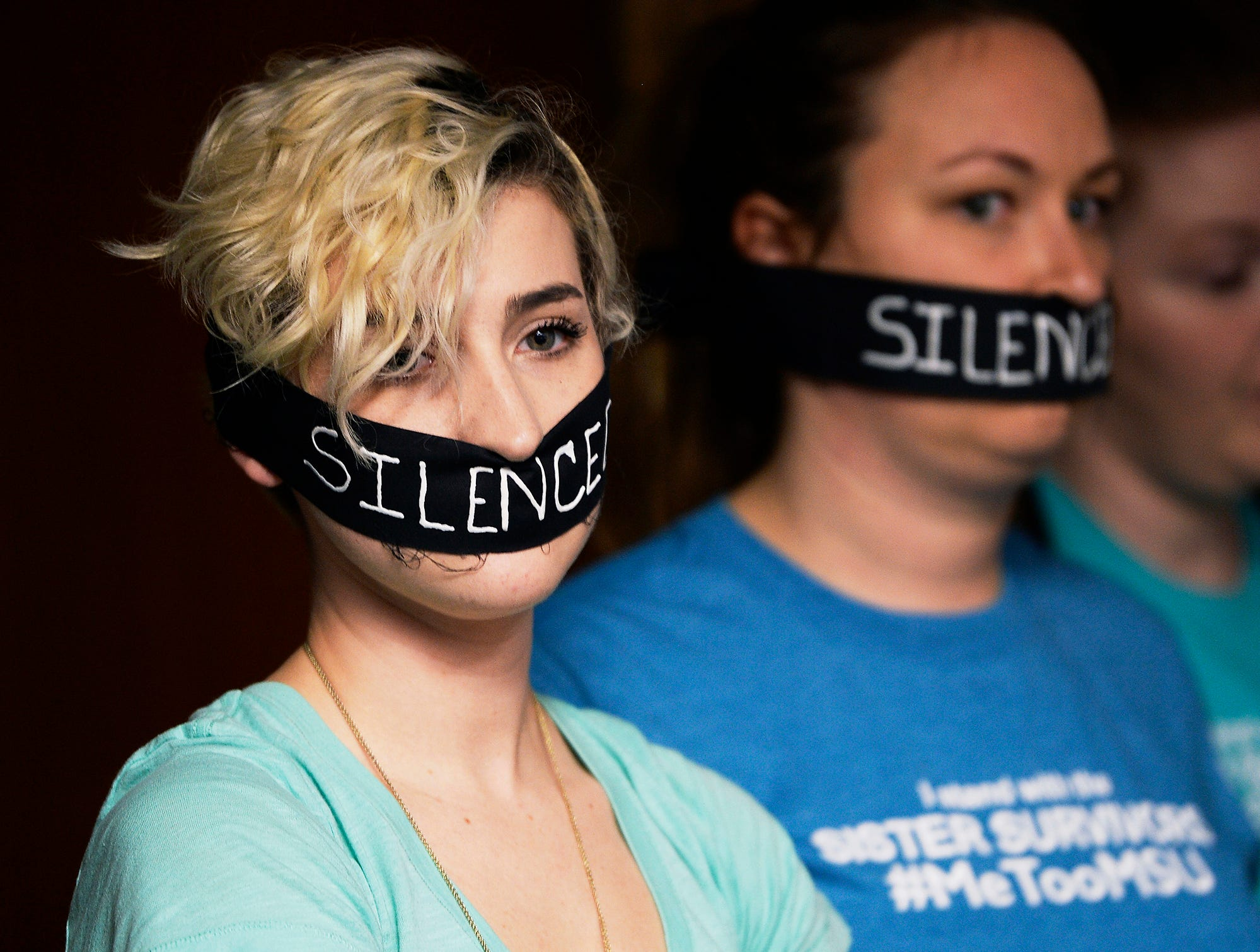 Survivors of sexual assaults by former MSU doctor Larry Nassar, Amanda Thomashow, left, 28, and Alex Neil-Sevier, 29, wear silence gags while listening to the Michigan State University Board of Trustees meeting, April 13, 2018, in East Lansing. They were unhappy that MSU president John Engler cut short another survivor's comments to MSU trustees on March 28.