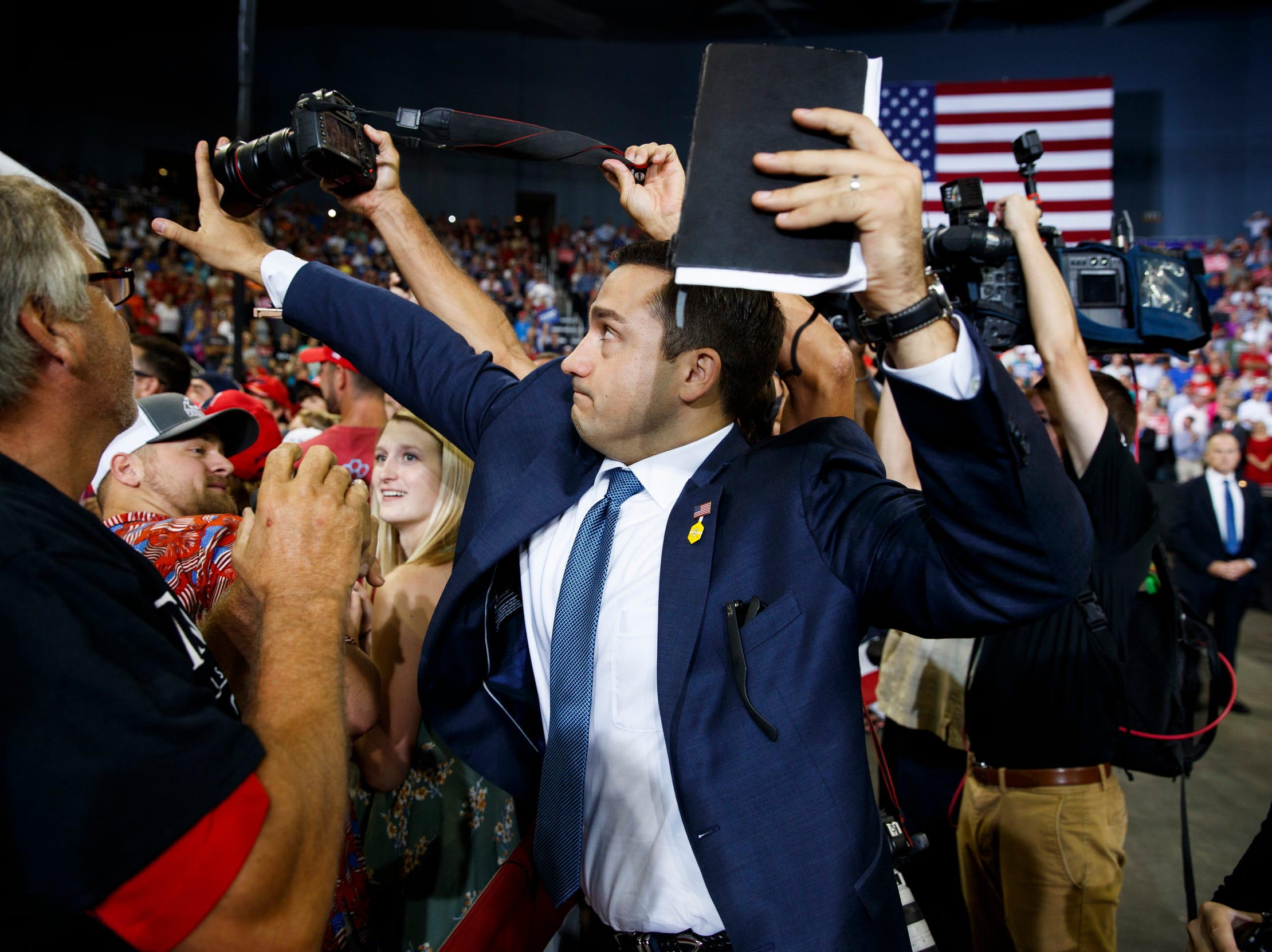 A volunteer member of the advance team for President Donald Trump blocks a camera as a photojournalist attempts to take a photo of a protester during a campaign rally in Evansville, Ind., on Aug. 30, 2018.