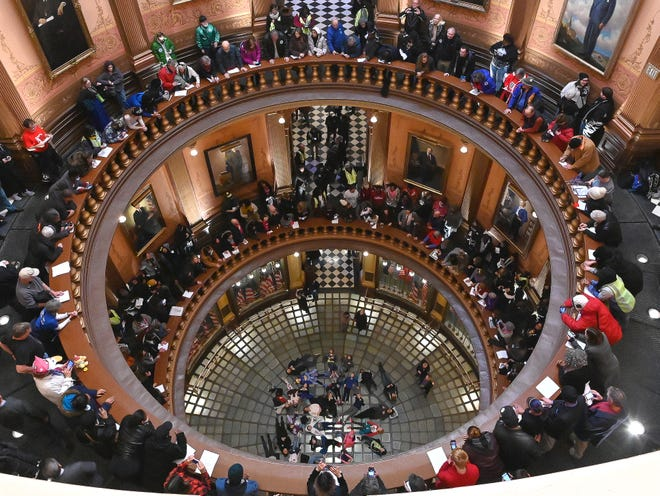 "In spite of the politics, a group of school kids visiting the Capitol lay on the floor of the Rotunda while demonstrators make noise and chant as the Michigan Senate and House of Representatives consider bills during the ""lame duck"" session in Lansing on December 12, 2019. Docents encourage kids to lie on the floor, which gives them an unparalleled view of the spectacular ceiling of the Rotunda."
