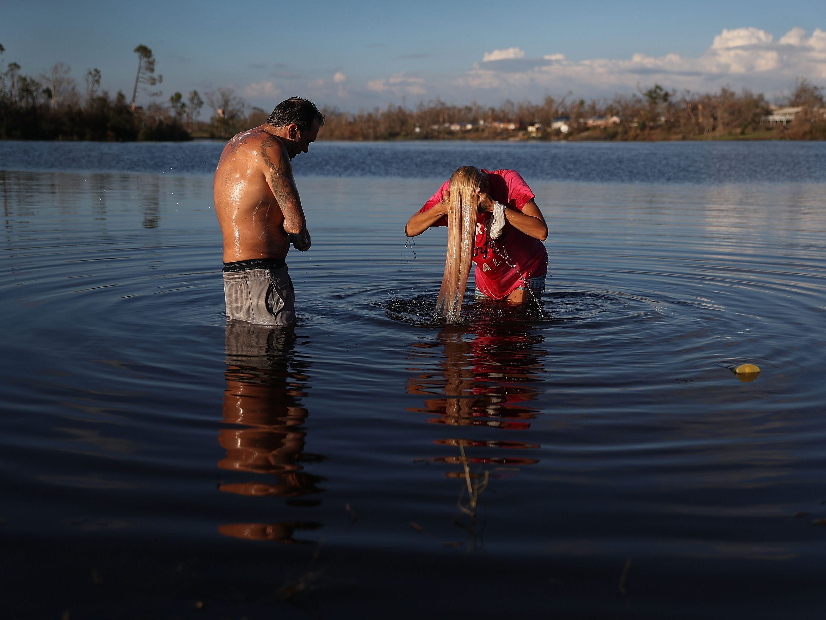 Justin Norman and Lisa Salle wash themselves in Lake Martin because their home has no running water after much of Panama City, Florida's infrastructure was damaged by Hurricane Michael on October 16, 2018. Michael slammed into the Florida Panhandle on October 10 as a Category 4 storm, causing widespread damage and claiming as many as 26 lives.