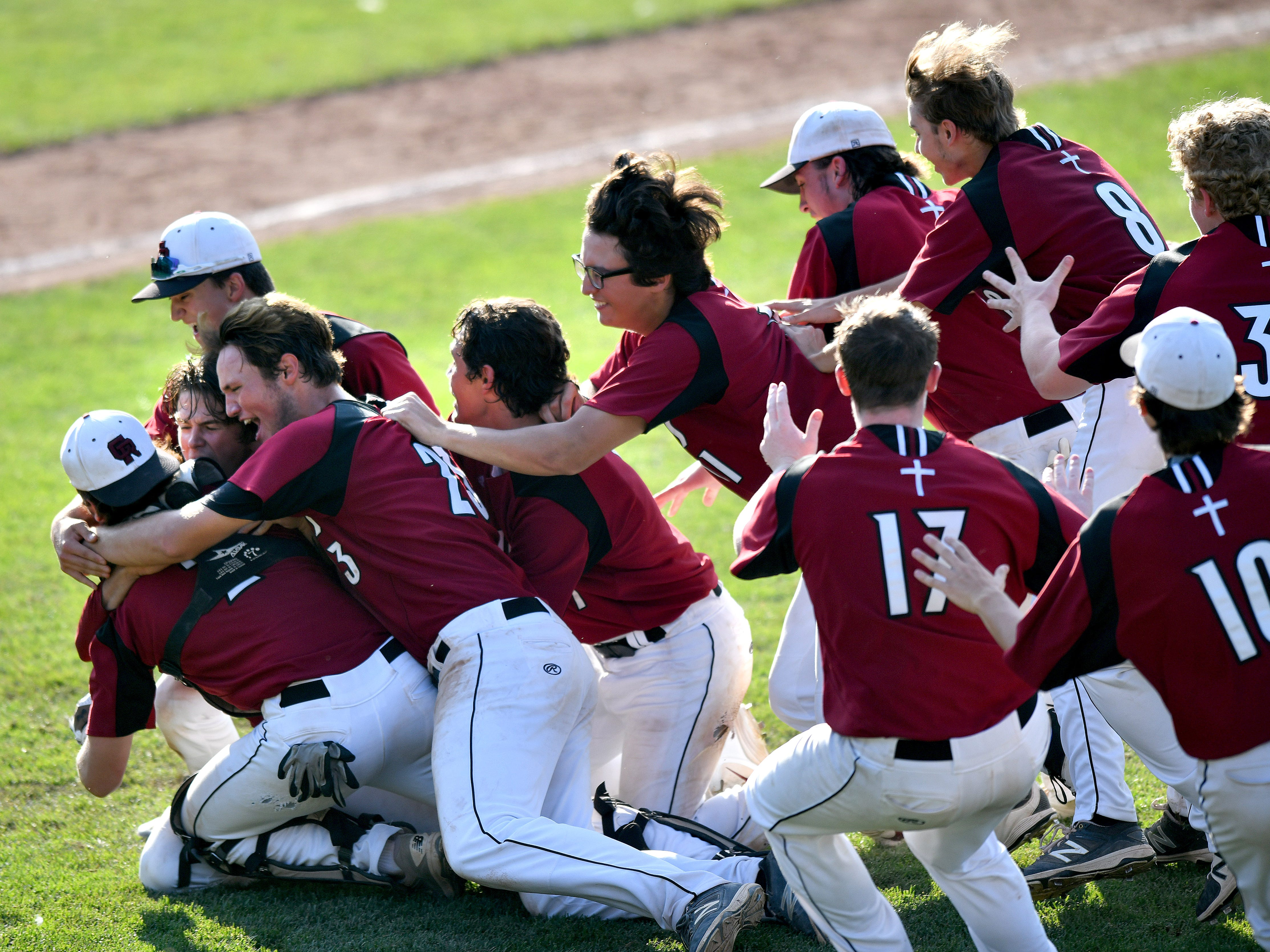 Riverview Gabriel Richard High School players pile on each other in celebration after they beat Madison Heights Bishop Foley, 3-0, in the MHSAA Division 3 baseball championship game at Michigan State University in East Lansing on Saturday, June 16, 2018.