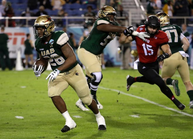 UAB running back Spencer Brown (28) runs as Northern Illinois defensive end Sutton Smith (15) is blocked during the first half.
