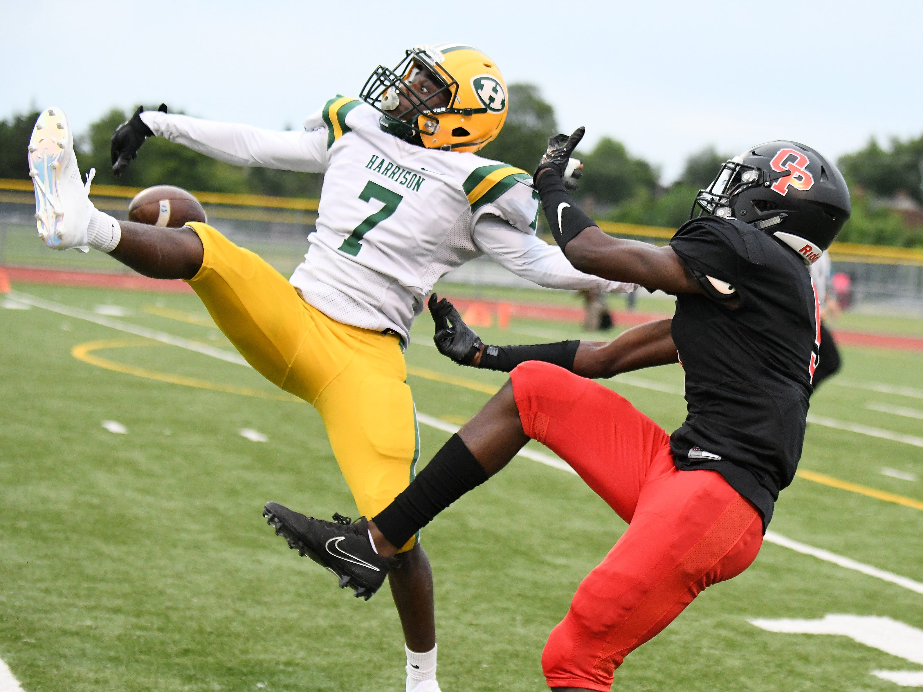 Looking a little bit more like ballet than football on this pass break up, Farmington Hills Harrison's Delwuan Gaston (7) breaks up a pass intended for Oak Park's Terrell Goff durinng a game at Oak Park High School on Sept. 7, 2018.  Both teams made the state playoffs. For Harrison it was the final season of one of the most dominant high school football programs in state history. The school will close at the end of this school year due to declining enrollment and consolidation.