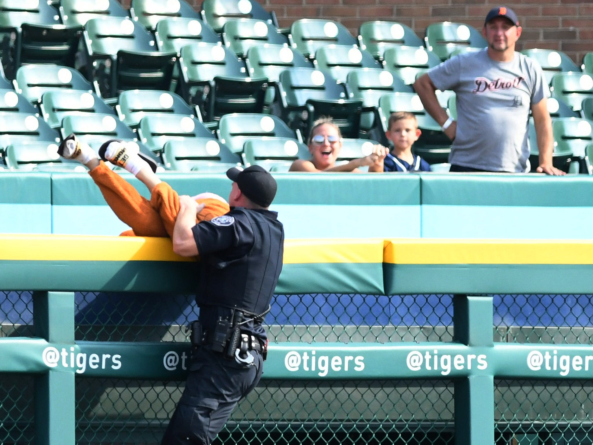 At the visiting bullpen wall, a Detroit police officer catches up with a man who ran onto the field in the ninth inning of a Tigers game against Minnesota Twins at Comerica Park in Detroit on Sept. 19, 2018.