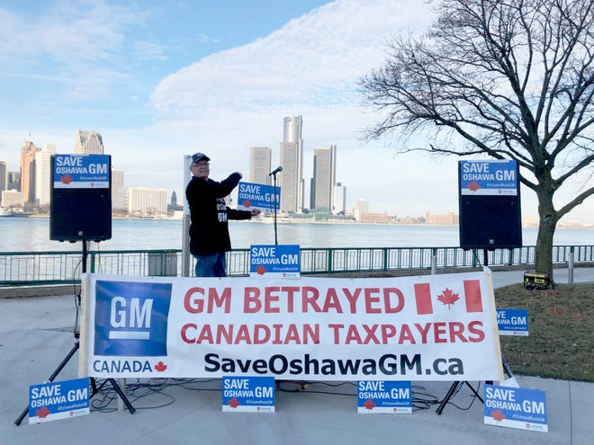 Unifor Canada posted this photo on social media Wednesday showing signs saying 'GM betrayed Canadian Taxpayers' and 'Save Oshawa GM,' positioned across the river from GM's headquarters.