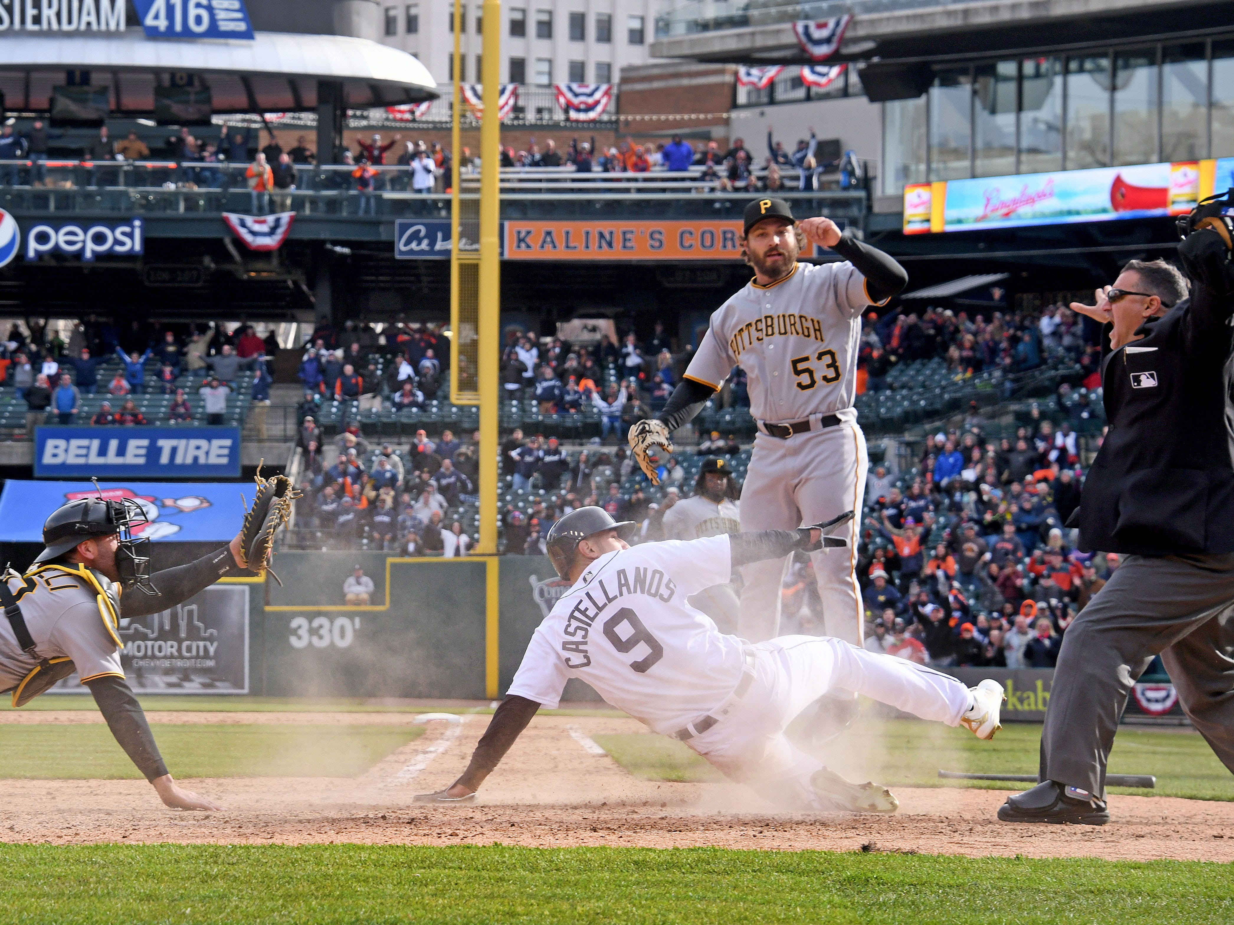 Nick Castellanos slides home as the ball arrives in the 10th inning at Comerica Park on Opening Day, Friday, March 30, 2018 against the Pittsburgh Pirates. Castellanos was initially ruled safe, then out, causing an uproar and costing the Tigers the game. The Pirates scored 3 runs in the 13th inning to beat Detroit 13-10.