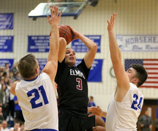 Luke Baldwin of Elmira takes a shot in between Hayden Robinson (21) and Max Keagle (24) of Horseheads on Dec. 18, 2018 at Horseheads Middle School.