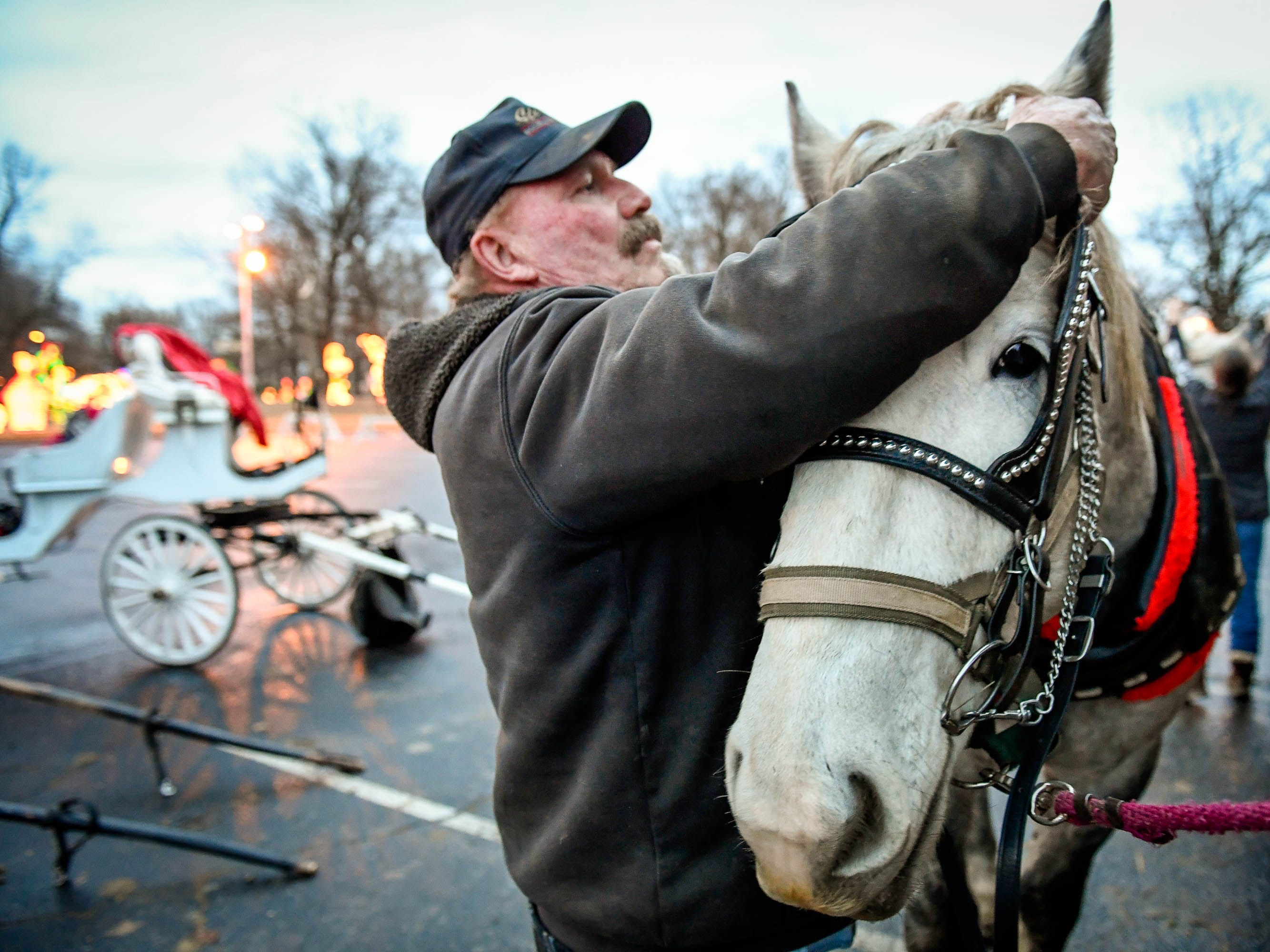 Randy O'Risky puts a harness on Chuck, one of the horses the Horseshoe Bend Carriage Company uses for carriage rides through the Ritzy's Fantasy of Lights in Garvin Park Tuesday, December 18, 2018.