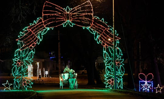 Shelia O'Risky, with the Horseshoe Bend Carriage Company, drives Queenie as she pulls a carriage load of visitors through the Ritzy's Fantasy of Lights in Garvin Park Tuesday, December 18, 2018.
